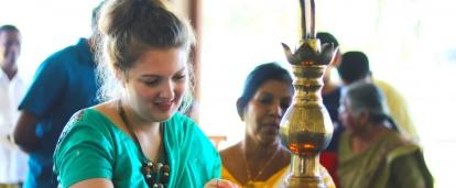 A volunteer lighs an oil lamp during a ceremony in Sri Lanka